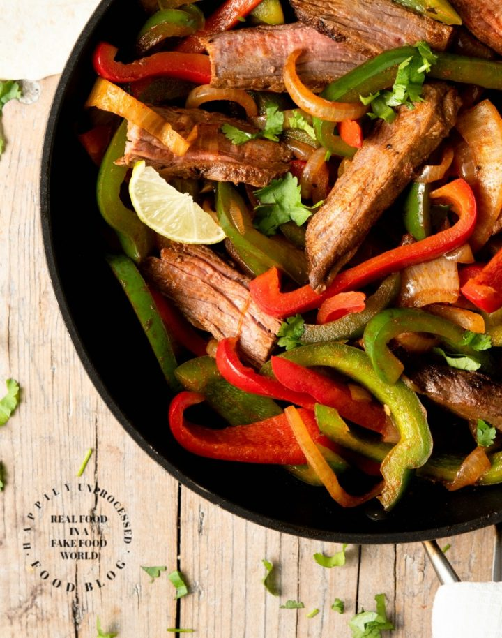 FLANK STEAK FAJITAS - perfectly grilled strips of flank steak with onions and peppers served with fresh tortillas, sour cream, guacamole and salsa #fajitas #happilyunprocessed
