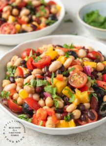 VIBRANT SUMMER 4 BEAN SALAD - 4 types of beans, colorful peppers, tomatoes, olives and red onion in a emulsified oil and vinegar dressing #summerrecipes #beansalad #potluck #healthy #summer #salads #happilyunprocessed