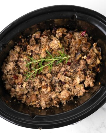 Slow cooker stuffing with sausage, cranberries, herbs and pecans. No turkey needed! The slow cooker makes the moistest best stuffing ever! #stuffing #thanksgiving #thanksgiving side dish # turkey #side dish