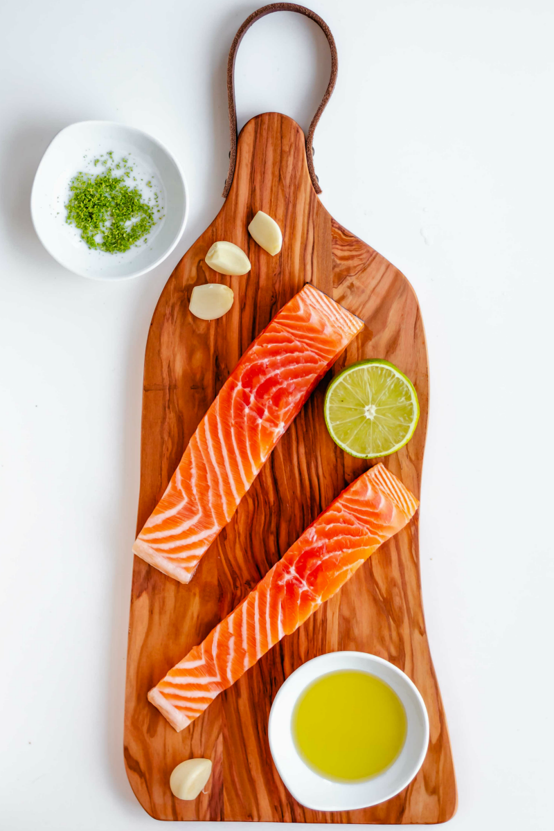salmon with mango and avocado salsa raw on cutting board - Healthy Grilled Salmon with Lime Mango Salsa