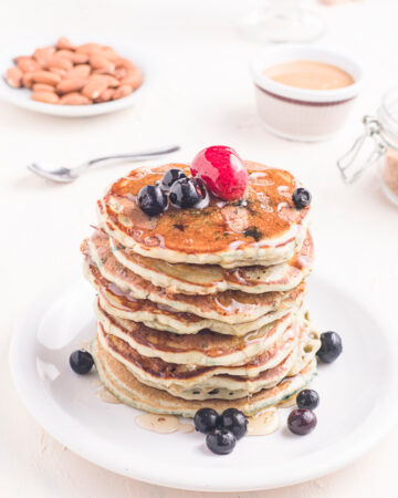 Homemade Blueberry Buttermilk Pancakes in a stack on a plate with fresh fruit