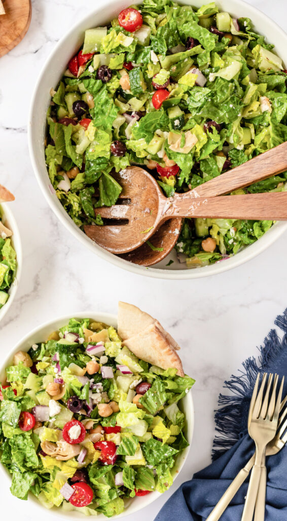 Chopped Greek Salad in a bowl and plates 566x1024 - Healthy Chopped Greek Salad with a Zesty Dressing