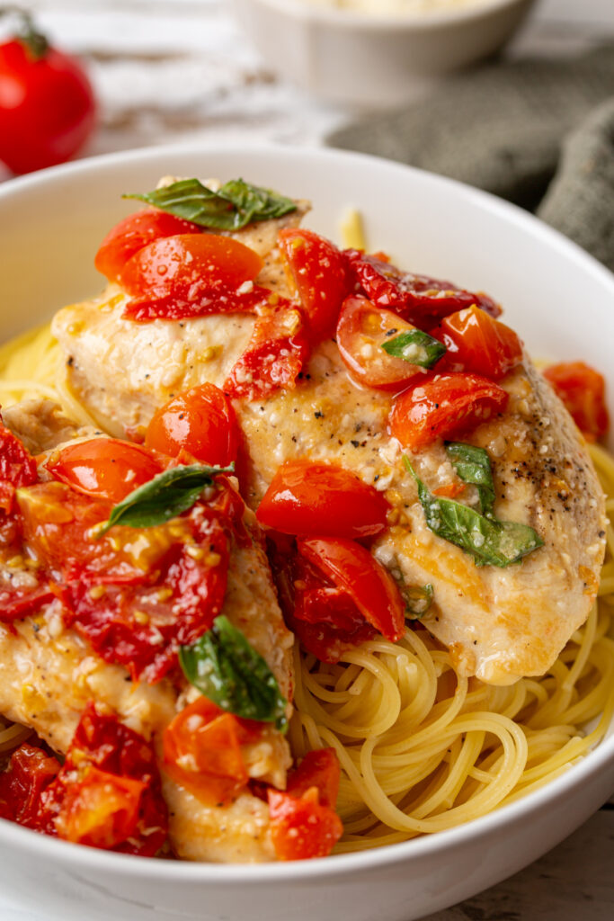 Tomato Basil Chicken in a garlic and butter sauce over garlic butter angel hair pasta in a white bowl 1 683x1024 - Tomato & Basil Chicken in a Garlic Butter Sauce