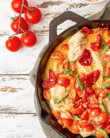 Tomato and Basil chicken in a garlic butter sauce in a cast iron skillet with sundried tomatoes