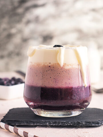 A healthy triple layered blueberry and banana smoothie topped with fresh whipped cream in a glass
